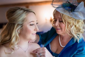 mother helping her daughter get ready on wedding day